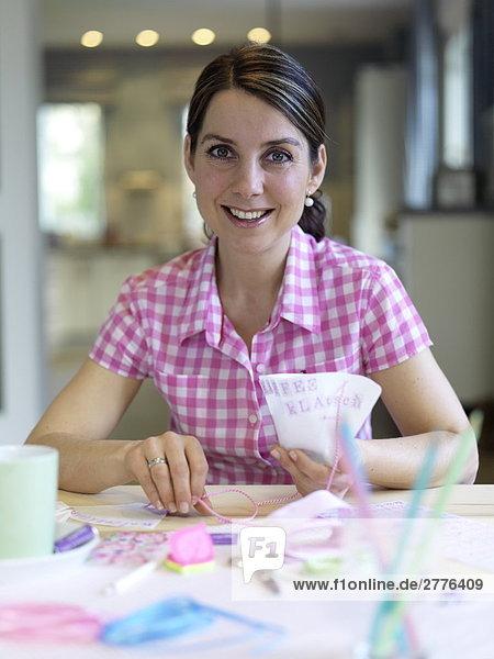 Porträt von Frau machen Einladungskarte am Tisch und lächelnd