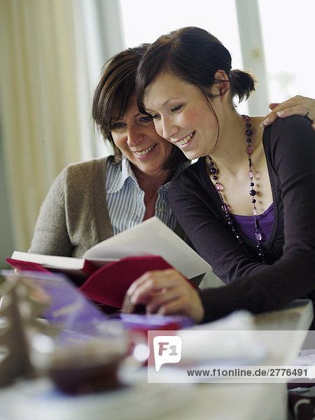 Frau und ihre Tochter lesen buchen Sie am Tisch