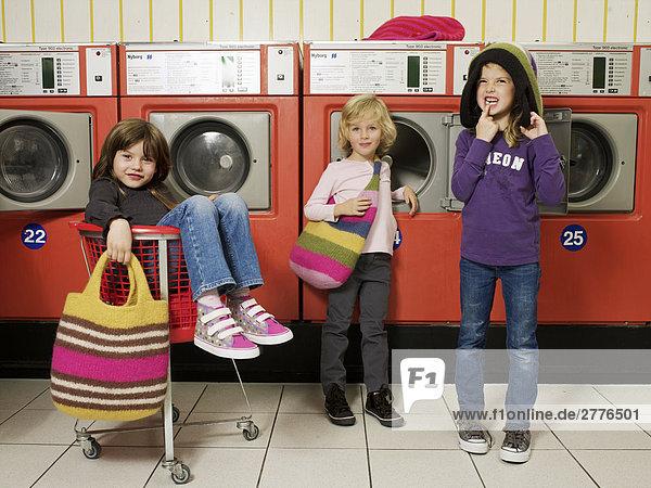 Drei Kinder an Waschmaschinen