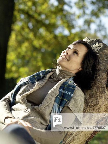 Reife Frau auf abgefallener Baum sitzen und lächelnd