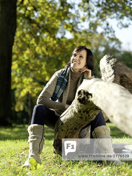 Mature woman sitting on fallen tree and smiling