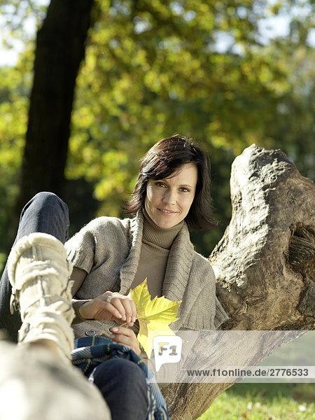 Portrait reife Frau auf abgefallener Baum sitzen und lächelnd