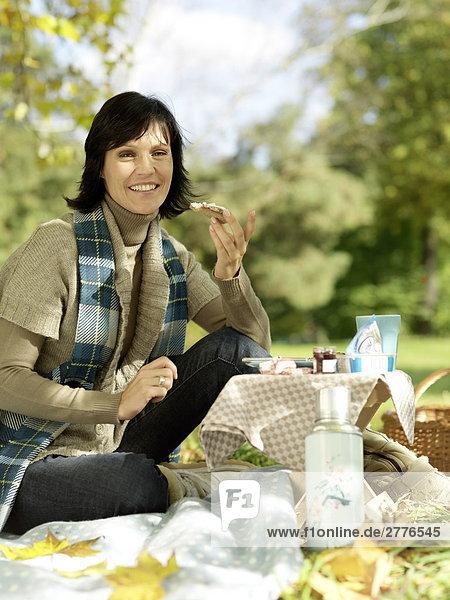 Portrait reife Frau hält Scheibe Brot und lächelnd im park