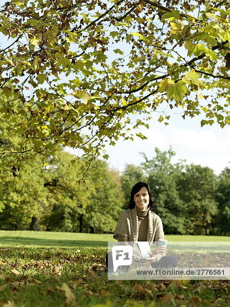 Portrait of mature woman holding book and smiling in park