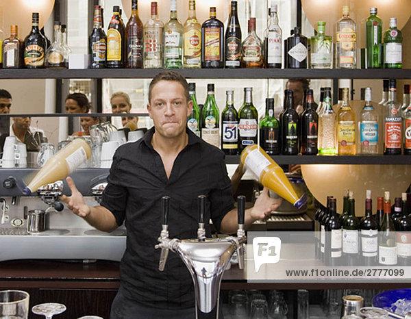Portrait des Barkeepers beim Spinnen von Getränken