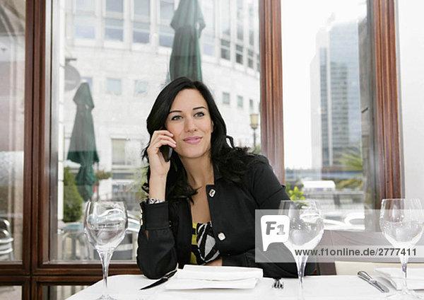 Geschäftsfrau auf dem Handy im Restaurant