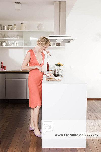Frau beim Zubereiten von Speisen in der Küche