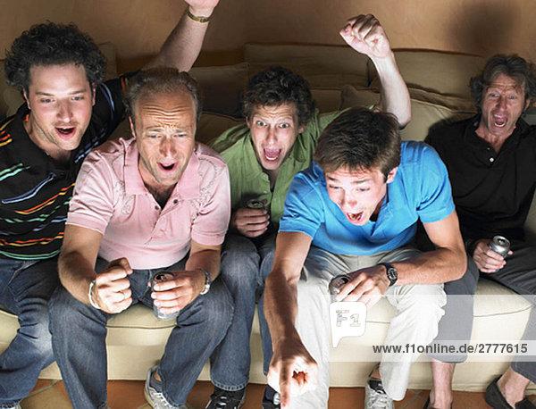 Männer schauen fern  halten Bier in der Hand