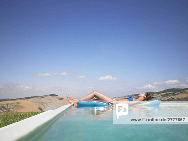 Frau ruht sich im Schwimmbad aus