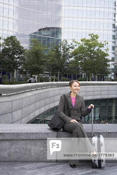 Geschäftsfrau sitzend mit Gepäck