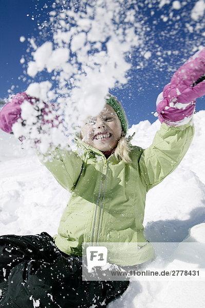 Porträt des Mädchens werfen Schnee und lächelnd