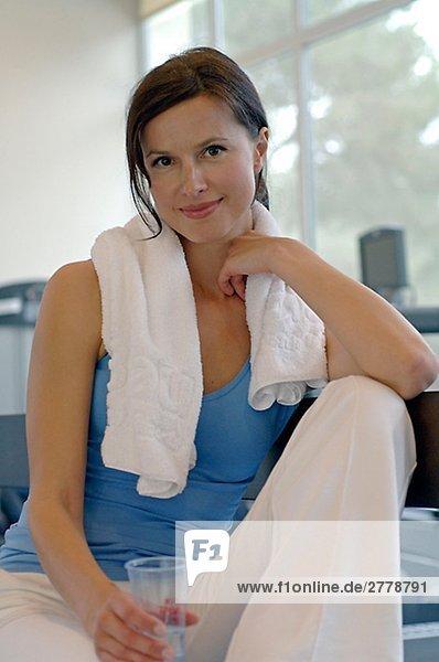Frau im Fitnessstudio mit Glas Wasser