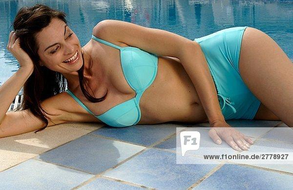 Frau im türkisfarbenen Bikini liegt am Rande eines Swimmingpools - Kopf aufgestützt