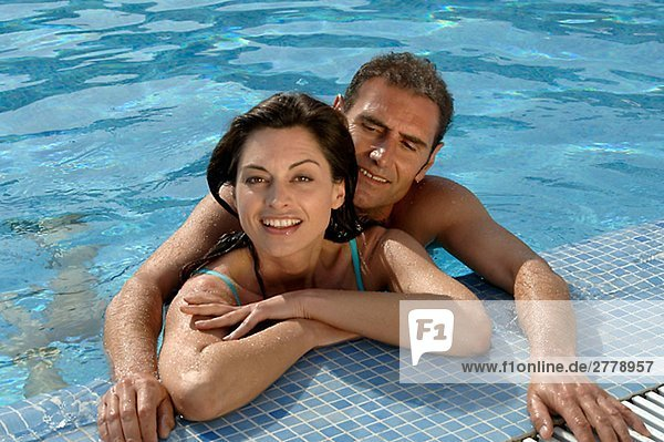 Paar im Swimming Pool am Beckenrand