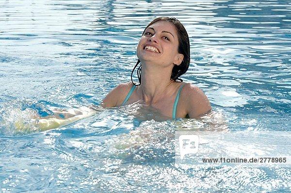 Frau planscht im Swimmingpool