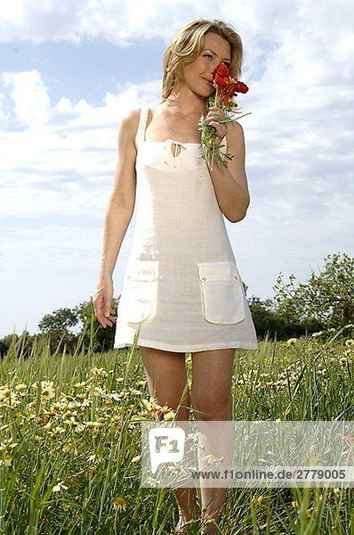 Frau steht auf einer Sommerwiese und riecht an einem Blumenstrauß