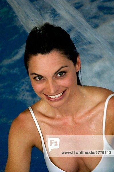 Frau im Schwimmbad unter einem Wasserstrahl