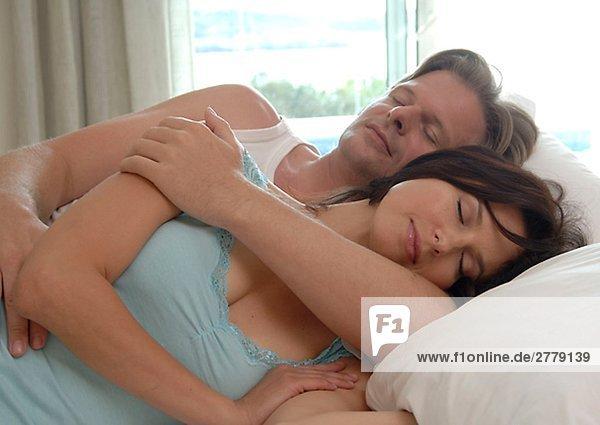 Paar liegt im Bett und schläft