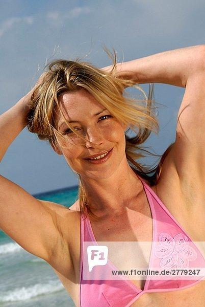 Frau am Strand mit Händen an den Haaren