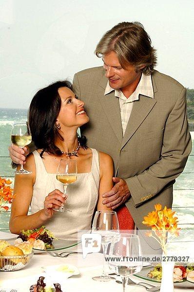 Paar am gedeckten Tisch am Meer mit Weingläsern