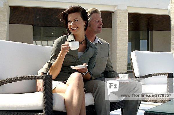 Paar sitzt auf einer Korbbank mit Tassen