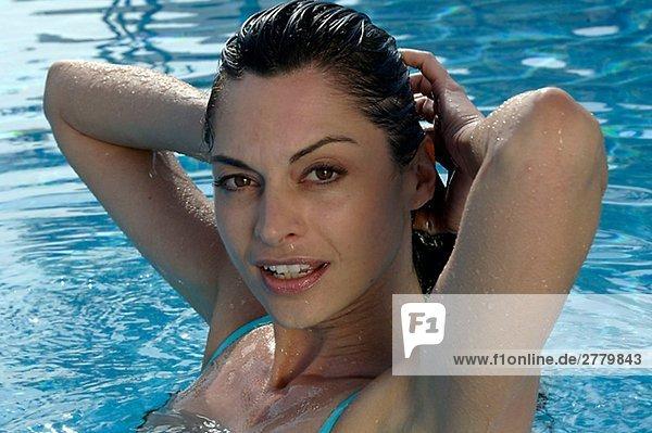 Frau im Wasser streicht sich die Haare zurück