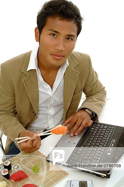 Asiate isst Sushi am Laptop