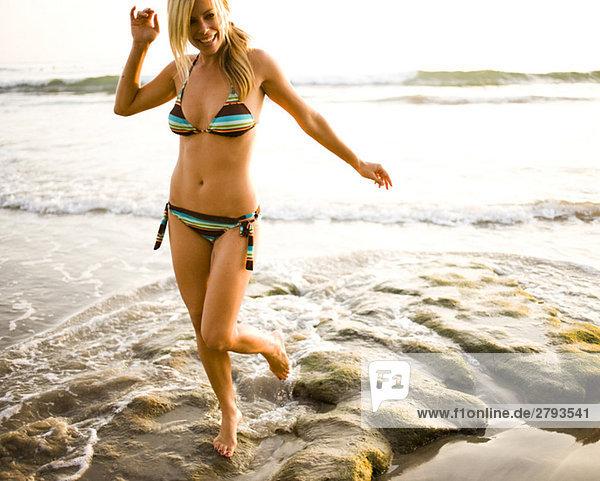 Frau in Bikini auf zerklüfteten Strand