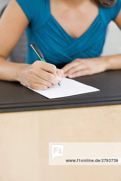 Close up of Latin American woman writing note at desk