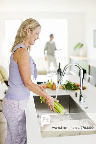 Frau waschen Sellerie in Küchenspüle