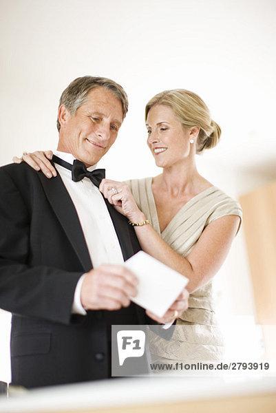 Paar in Abendgarderobe hält Hochzeitseinladung