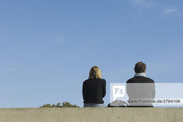 Paar auf Ledge  Rückansicht sitzend Paar auf Ledge, Rückansicht sitzend
