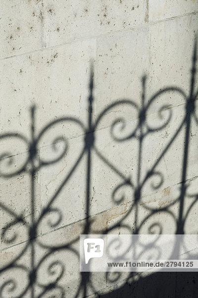 Schatten des verzieren Zaun an Wand