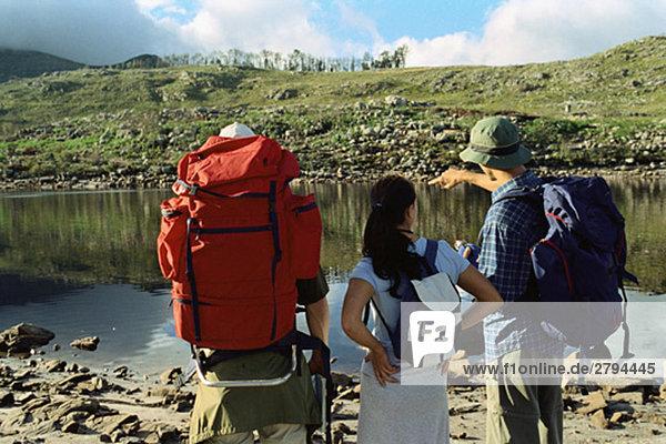 Wanderer entscheiden  wie sie den Teich überqueren  Rückansicht