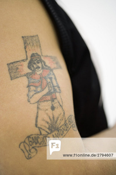 Tattoo von Gauchito Antonio Gil (Little Gaucho Gil) auf dem Bizeps des Mannes