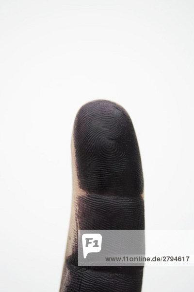 Finger mit schwarzer Farbe überzogen