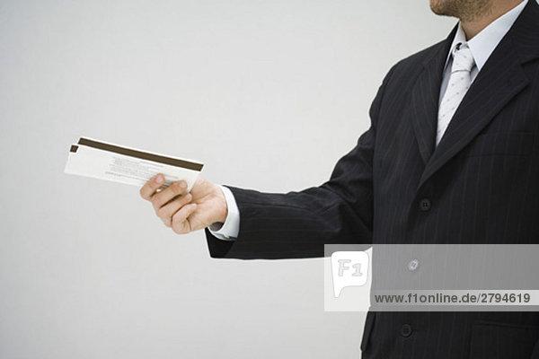 Mann im Anzug hält Tickets aus  Seitenansicht