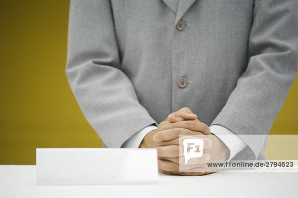 Mann im Anzug steht an der Theke neben einem leeren Schreibtischschild.