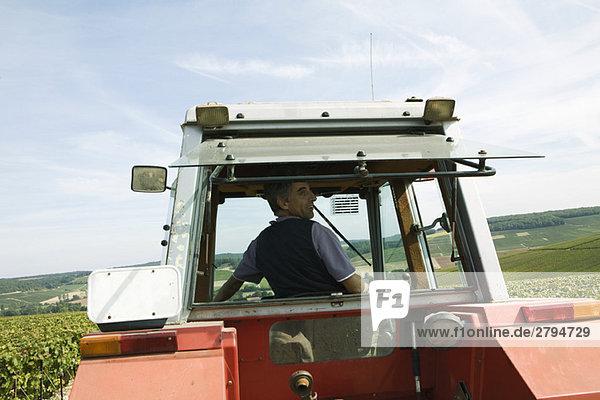 Frankreich  Champagne-Ardenne  Aube  Mann fährt Traktor  Rückansicht