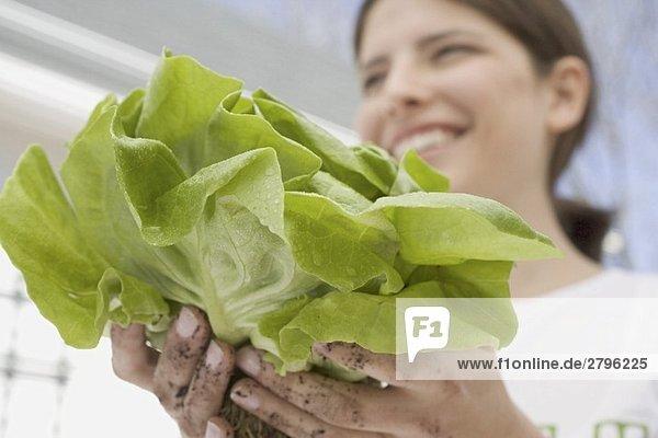 Junge Frau hält frischen Kopfsalat aus dem Garten