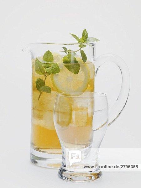 Eistee mit Zitronenscheiben und frischer Minze im Glaskrug