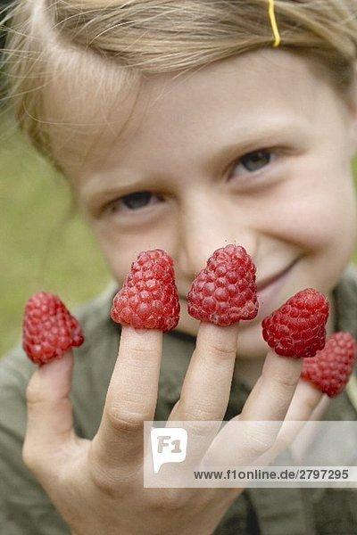 Mädchen mit Himbeeren auf den Fingern