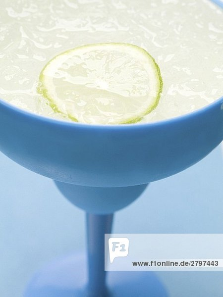 Frozen Margarita with slice of lime in blue glass