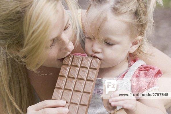 Mutter und kleine Tochter beissen in eine Tafel Schokolade Mutter und kleine Tochter beissen in eine Tafel Schokolade