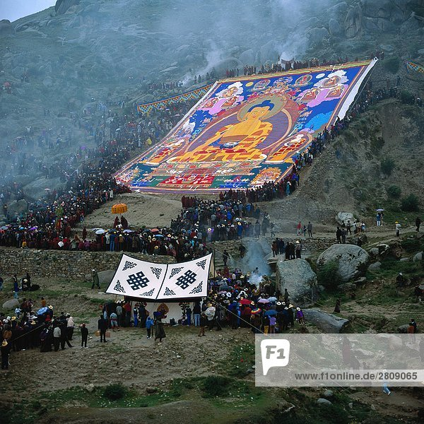 Crowds looking at woven Buddha  Tibet
