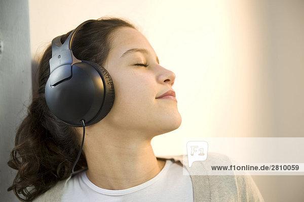 Mädchen tragen Kopfhörer und Musik zu hören