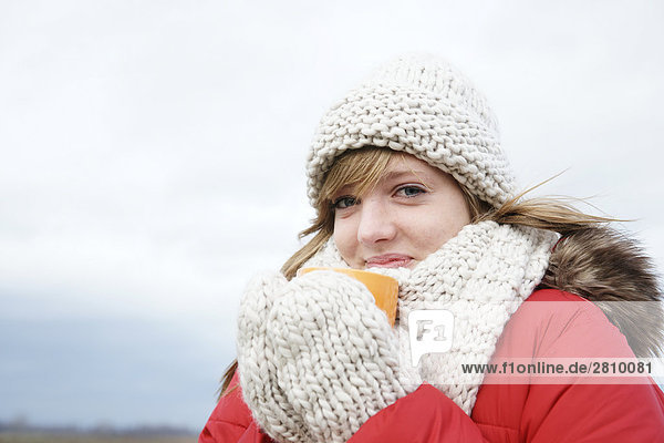 Portrait of teenage girl drinking hot chocolate in warm clothing