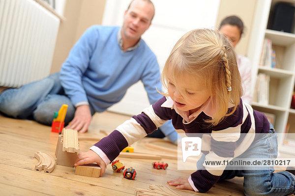 Girl playing with Spielzeug mit ihren Eltern hinter ihr