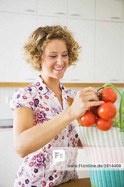 Frau Tasche Tomate herausnehmen