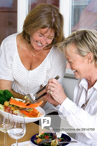 Two smiling mature women during a dinner Sweden.